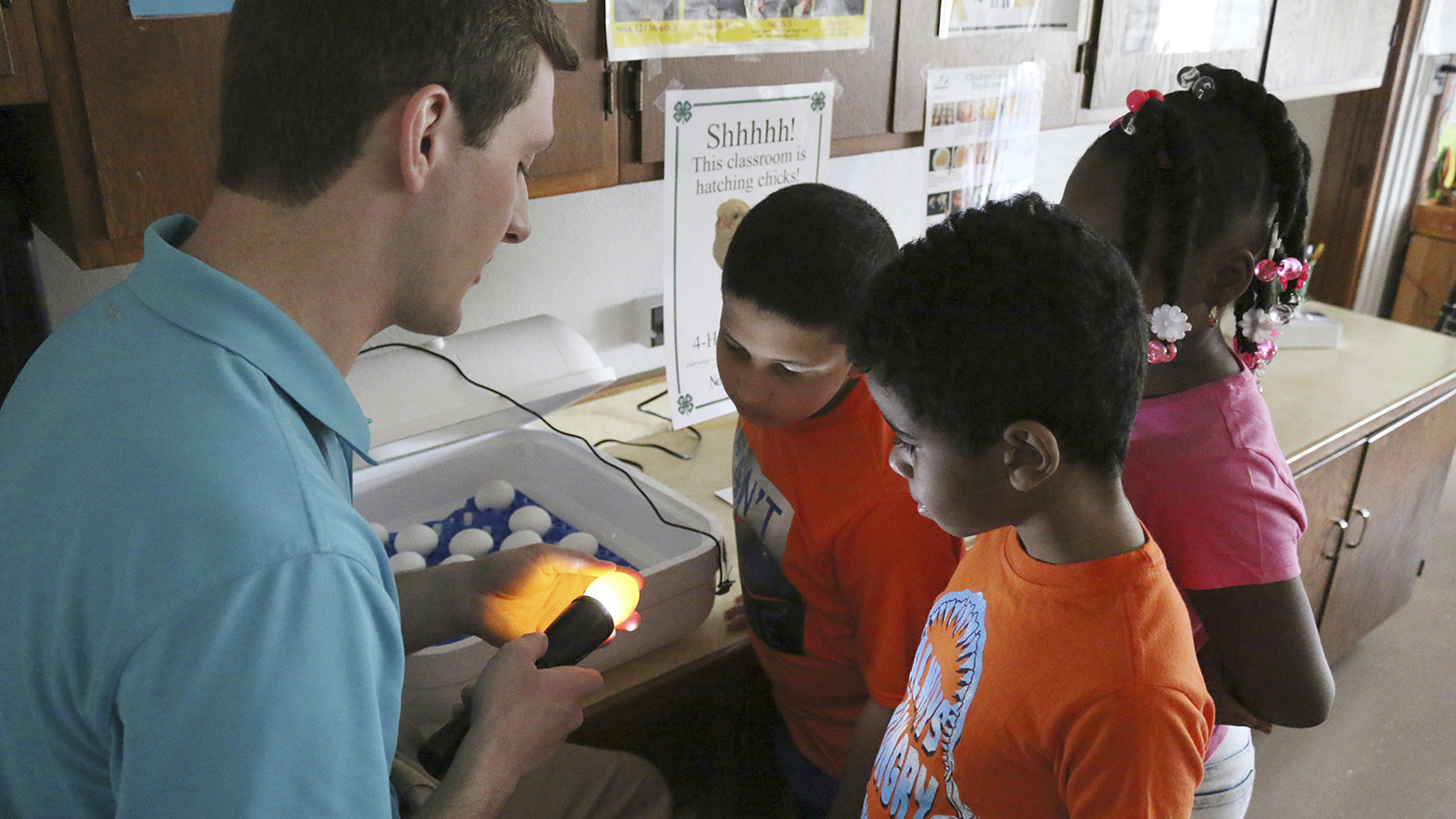 3 youth looking at adult who is holding a light up to a chicken egg