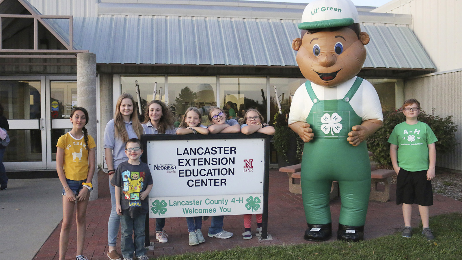 Lil Green mascot with group of kids