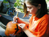 Girl Decorating a Jack-O-Lantern Pumpkin