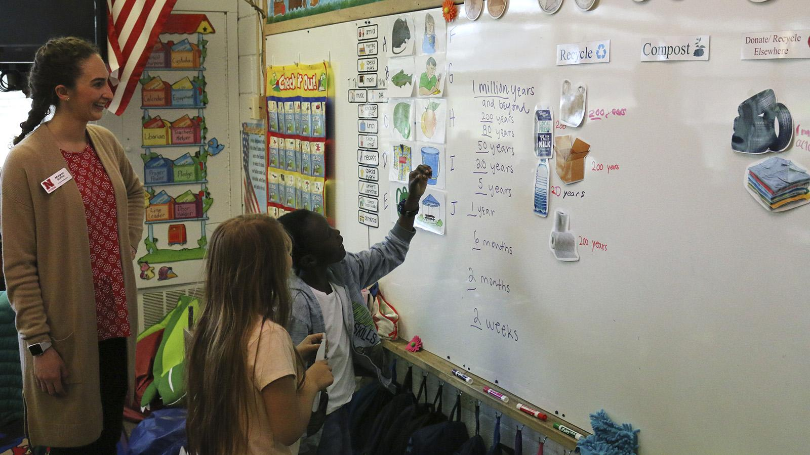Two students with recycling flash cards at a white board