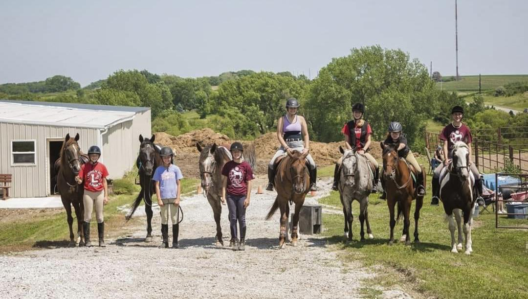 Youth lined up riding or standing next to their horses