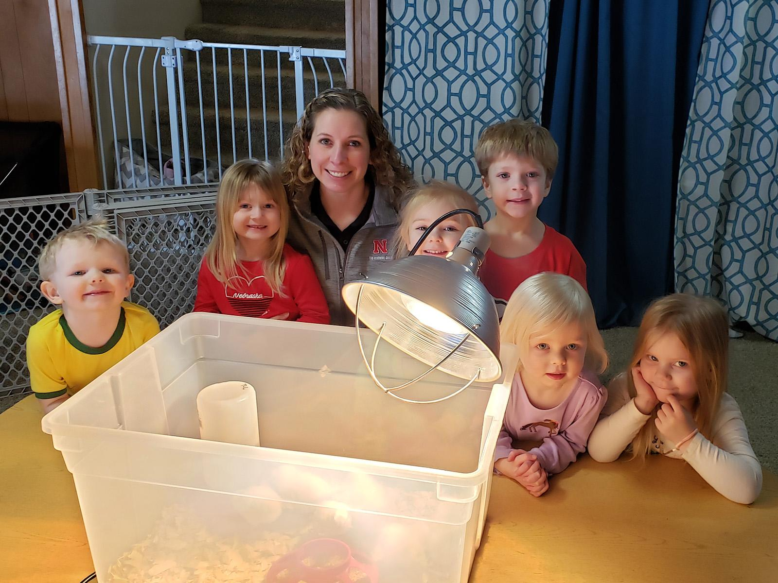 Group of young children behind a tote that has baby chicks in it