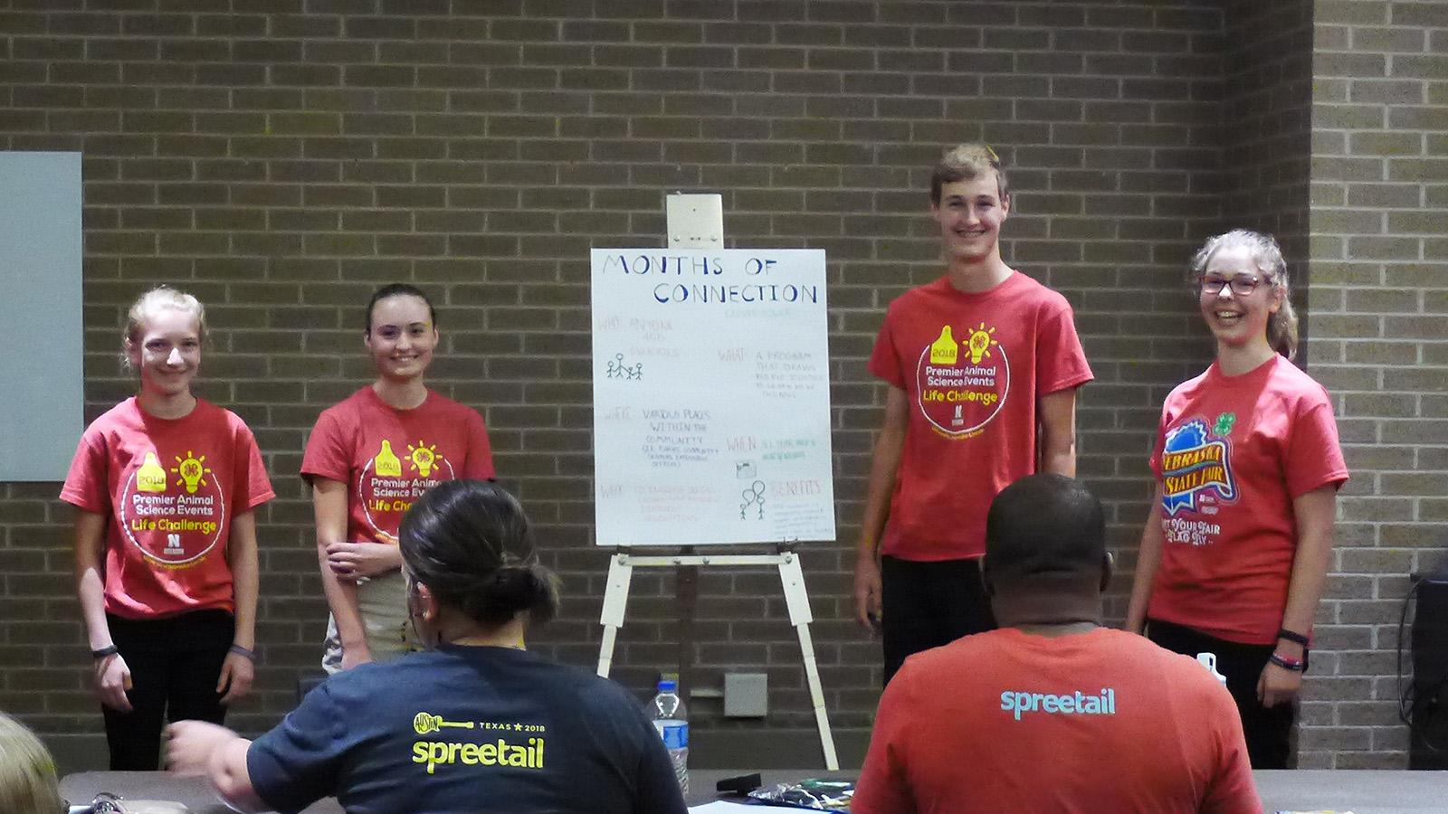 Four youth with a poster standing before two judges