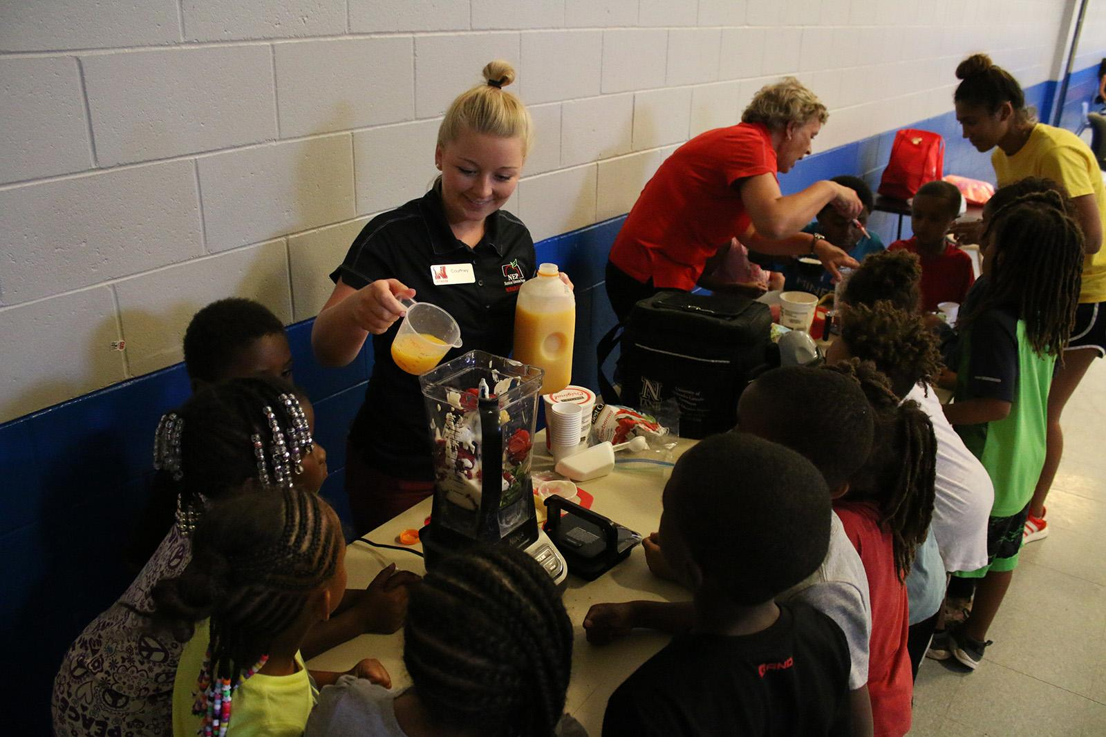 Group of youth helping make smoothies in blenders
